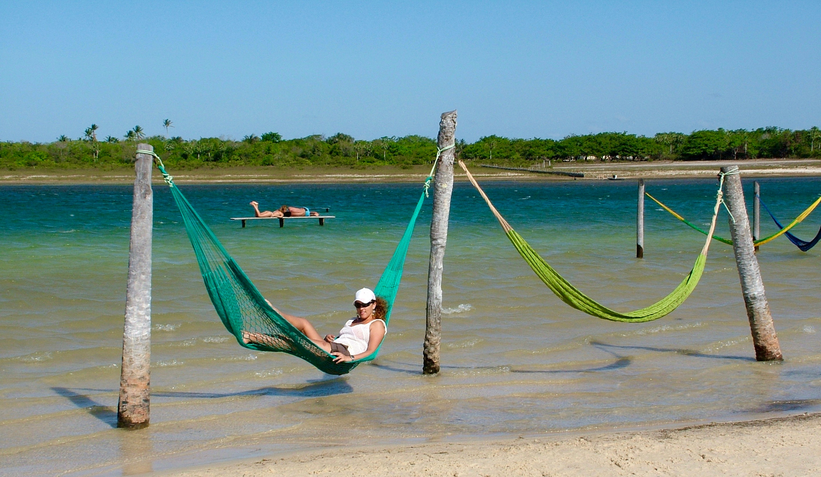 Tatajuba, some brightly coloured hammocks hang above the pleasent warm waters.