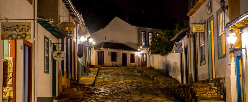 Minas Gerais, a cobbled street lit by street lamps in the evening.