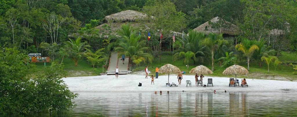 A shot of the Amazon eco-park, people enjoying the beach on the edge of the lake.