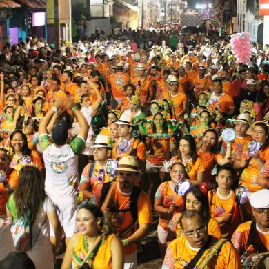 Crowd dressed in orange at précarnaval in Fortaleza.