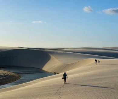 "A group of people walking along ""lencois maranheses."""