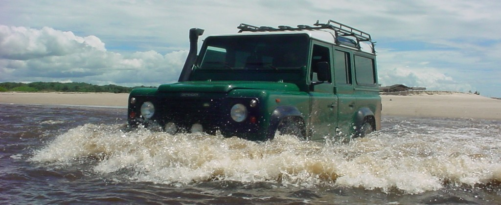 A 4x4 jeep, splashing through the water in Brazil.