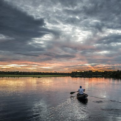 A sunset view of a boar paddling along the River Negro.