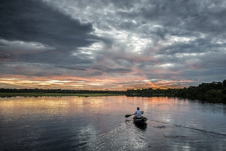 A man paddles his piroque into the sunset.