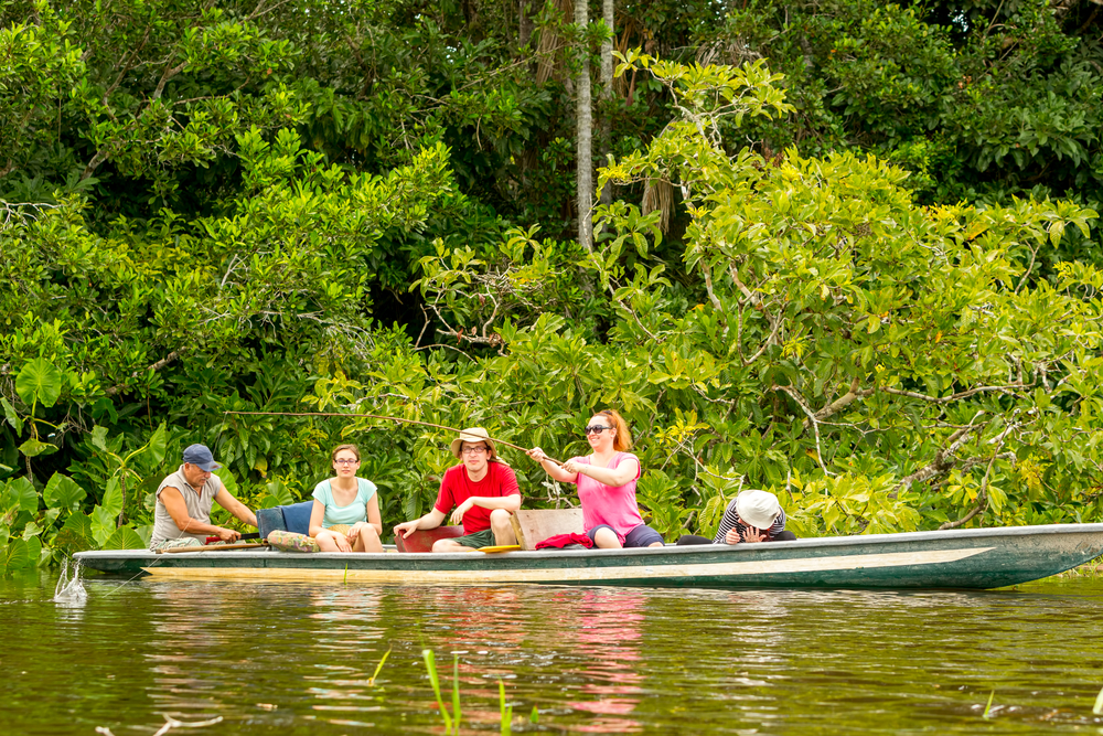 Some tourists piranha fishing from a boat accompanied by a guide on the Amazon river.