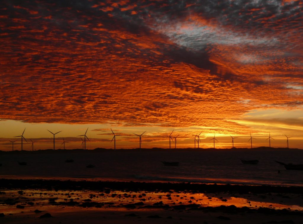 The sunset sets the sky in fire with a windfarm in the background.