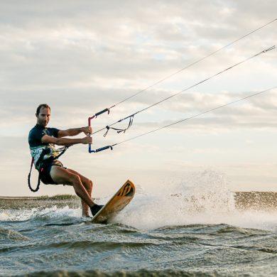 Kitesurfer rides on a surfboard style board.