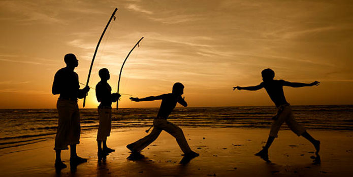 Four people play Capoeira, a Brazilian sport/martial-art/dance on the beach at sunset.