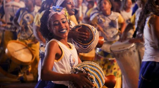 A woman plays a drum during the night of the silent drums in Recife.